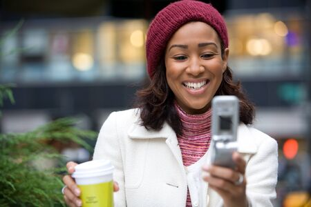 An attractive business woman checking her cell phone in the city Stock Photo - 4548538