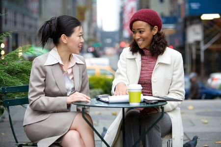 business pitch: Two business women having a casual meeting or discussion in the city.  Stock Photo