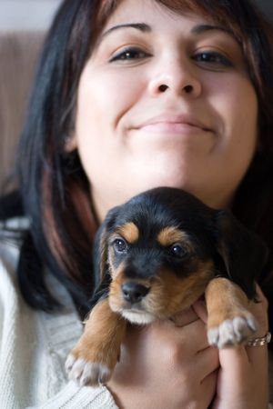 A young woman holding her cute mixed breed puppy - half beagle and half yorkshire terrier.  Shallow depth of field with stronger focus on the puppy. Stock Photo - 4593684