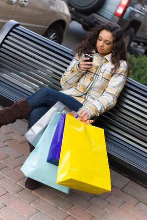 An attractive young woman checking her cell phone while out shopping in the city.  She might be texting or surfing the internet. photo