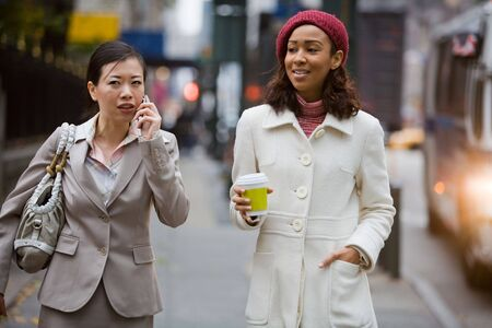 phone business: Two business women walking in the big city. One is on her cell phone.