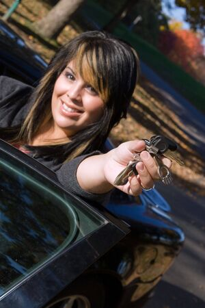 A young girl happily shows off the keys to her new car. Shallow depth of field with focus on the hand. photo