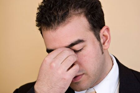 might: Young man with a headache. He might be experiencing intense stress over a time of economic downturn or other financial hardship. Stock Photo