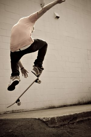 A young skateboarder doing a stunt in an urban area. Stock Photo - 4632383