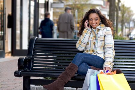 sexy girl sitting: An attractive girl talking on her cell phone while out shopping in the city. Stock Photo