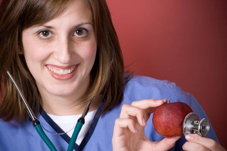 A young nurse is holding her stethoscope onto a red apple.  An apple a day keeps the doctor away. photo