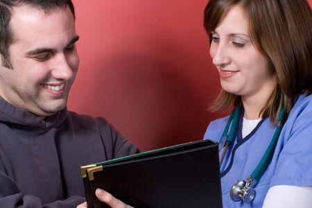 lpn: A young nurse sharing results with her patient during his visit. Stock Photo