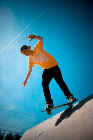 A young man skateboarding down a ramp at the skate park. Stock Photo - 4652351