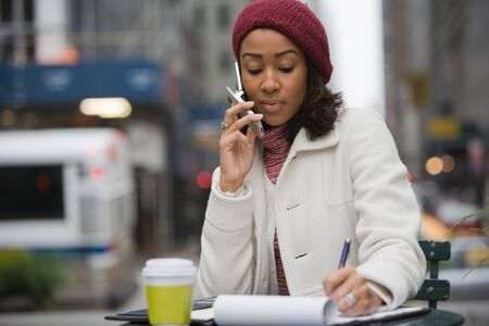 An attractive business woman talking on her cell phone and writing something down in her notes. photo