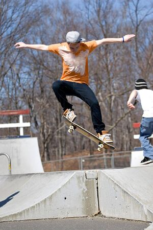 Portrait of a young skateboarder performing a jump at the skate park. Stock Photo