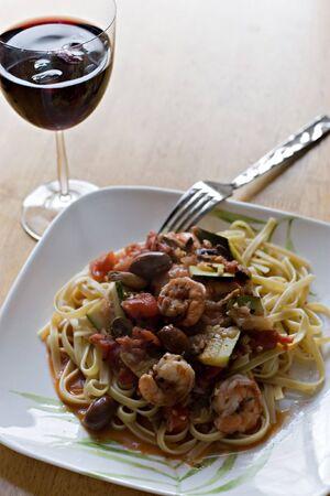 plato del buen comer: Un delicioso plato de pasta de camarones y, junto con un vaso de vino tinto.