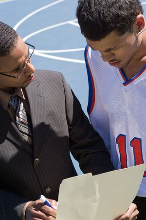 A basketball coach in a business suit sharing a play with a player on the team.   He could be also be recruiter trying to get him to sign a contract. Stock Photo - 4683963