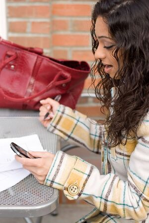 An attractive Indian woman texting or searching the web on her cell phone while seated at a table outdoors. photo
