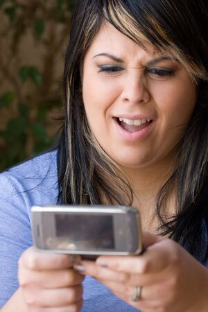plus sized: A young woman shocked at what she is reading on her cell phone.  Shallow depth of field.