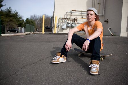 skater boy: A young skater resting on his board.