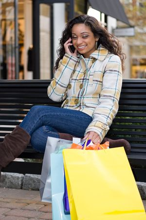 An attractive girl talking on her cell phone while out shopping in the city. photo