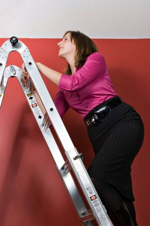 rungs: A young business woman rising to the top of this symbolic corporate ladder. Stock Photo
