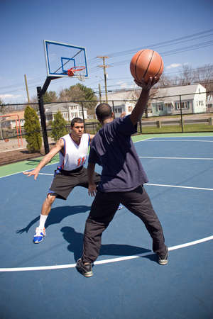 A young basketball player is taunting his opponent with the ball while playing one on one. Stock Photo - 4762827
