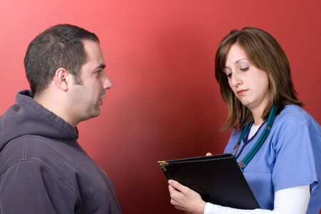 lpn: A young nurse talks to a concerned patient during his visit.
