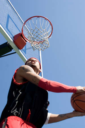 layup: A young basketball player under the rim going for a reverse slam dunk.  Shallow depth of field with stronger focus on the goal.