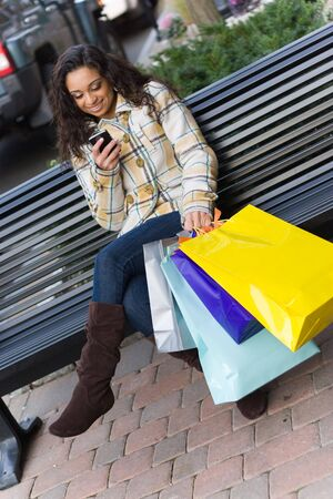 An attractive young woman checking her cell phone while out shopping in the city.  She might be texting or surfing the internet. Stock Photo - 4822231