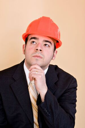 home builder: A man in a business suit and hard hat thinking about something. He could be a custom home builder or even an engineer or architect.
