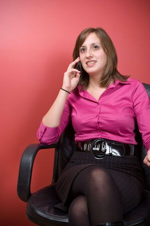 A young business woman talking on a cell phone while seated in her chair at work.