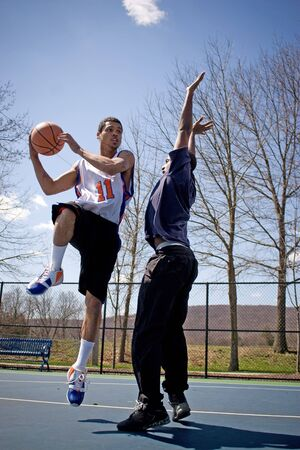 sportsmen: Two young basketball players compete fiercely against each other. Stock Photo