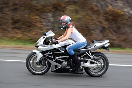 A pretty blonde girl in action driving a motorcycle at highway speeds. Stock Photo - 4854756