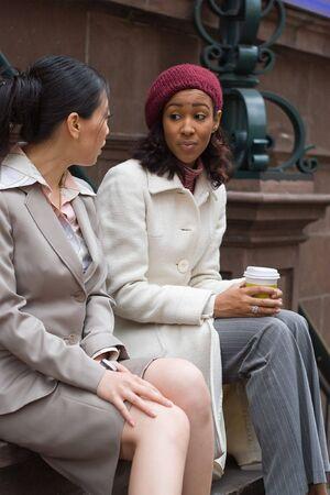 amigas conversando: Dos mujeres con una pareja ocasional reuni�n o discusi�n en la ciudad. Profundidad de campo. Foto de archivo