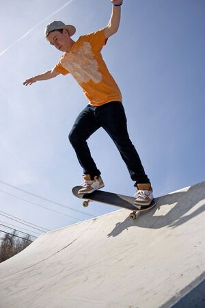 A young man skateboarding down a ramp at the skate park. Stock Photo - 4876410
