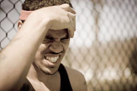アスリート: 若い選手は怒りや痛みで彼の額をつかみます。 写真素材