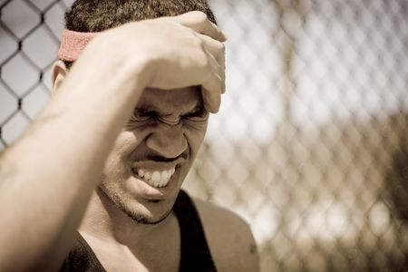 Een jonge atleet grijpt naar zijn voorhoofd in woede of pijn.