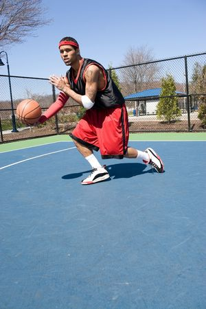 A young basketball player driving to the hoop demonstrating his ball handling skills. Stock Photo - 4876382