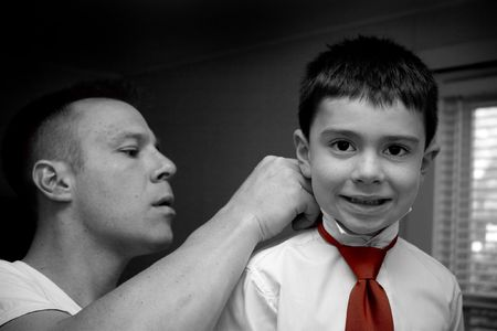 A groom helps his son get ready by putting on his tie. photo