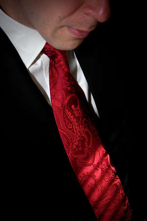 Closeup detail of a groom or business man in a tuxedo with a red tie. photo
