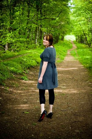 A young woman walking through a wooded path. photo