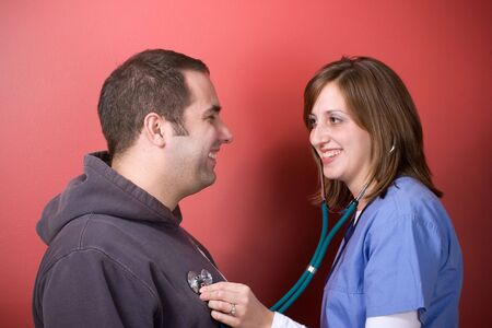 A young doctor or nurse listening to the heartbeat of her patient with her stethoscope during an office visit. photo