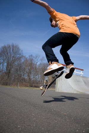 boy skater: Portrait of a young skateboarder performing a trick at the skate park.