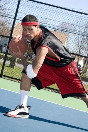 A young basketball player driving to the hoop demonstrating his ball handling skills. Stock Photo - 4918096