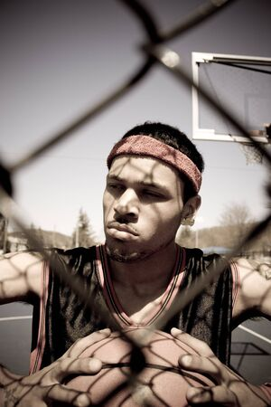 A young basketball player gripping the ball tightly as viewed through the chain linked fence. photo