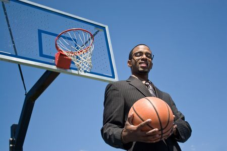 African American man in a business suit posing with a basketball.  He could be a coach player recruiter or trainer. Stock Photo