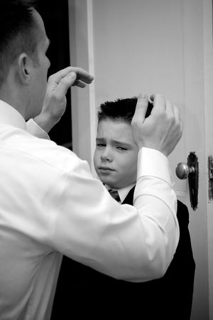A groom helps his son get ready by doing his hair. photo