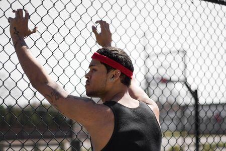 chainlinked: Een jonge basketbal leunend tegen de keten gekoppeld hek op het basketbalveld.