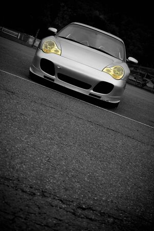 A silver sports car with the yellow headlights highlighted in selective color.  Plenty of copyspace for your text. Stock Photo - 4964473