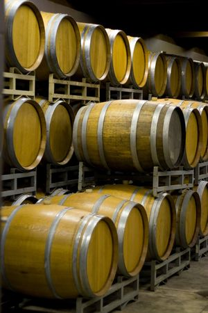 vino: A vineyard cellar where barrels of wine age in stacked rows.