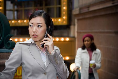 An attractive Asian business woman talking on her cell phone in the city. Stock Photo - 4956067