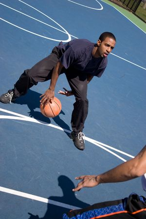baller: A young basketball player posts up against his opponent during a one on one basketball game.
