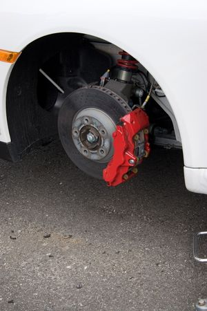 stopping: Closeup detail of the wheel assembly and six piston calipers on a modern sports car braking system. The rim is removed showing the front rotor and caliper.
