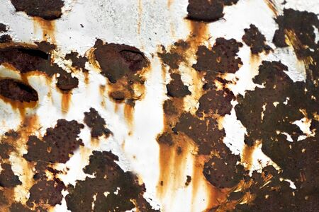 Closeup of rusted metal with chipped paint and holes. photo